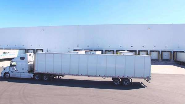 Transport trucks leaving a loading dock Royalty-free stock video