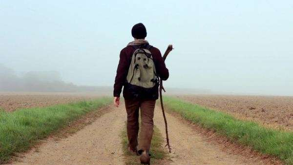 A traveler with a walking stick journeys off into the mist on a country trail. Royalty-free stock video