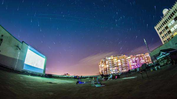 Timelapse of people watching movies in open air on the roof of the building with startrails on a backround ODESSA - JULY 21: (TIMELAPSE) People watching movies in open air on the roof of the building with startrails on a backround on July 21, 2012 in Odessa, Ukraine. Royalty-free stock video