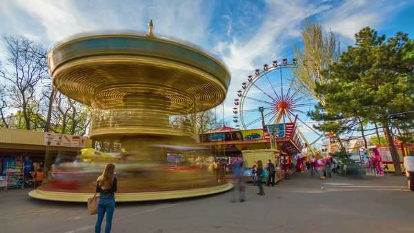 Timelapse of parents and kids on carousel merry-go-round with ferris wheel Royalty-free stock video