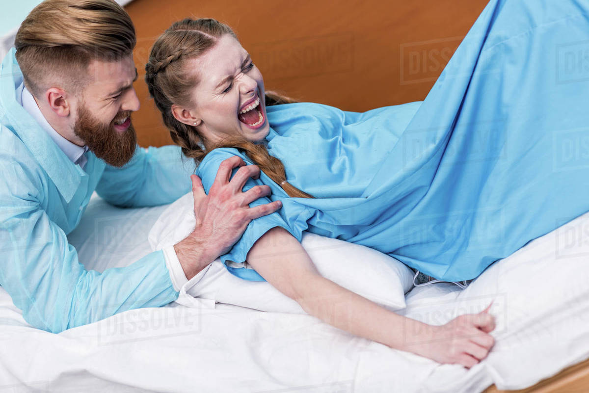 Pregnant woman giving birth in hospital while man hugging her stock photo
