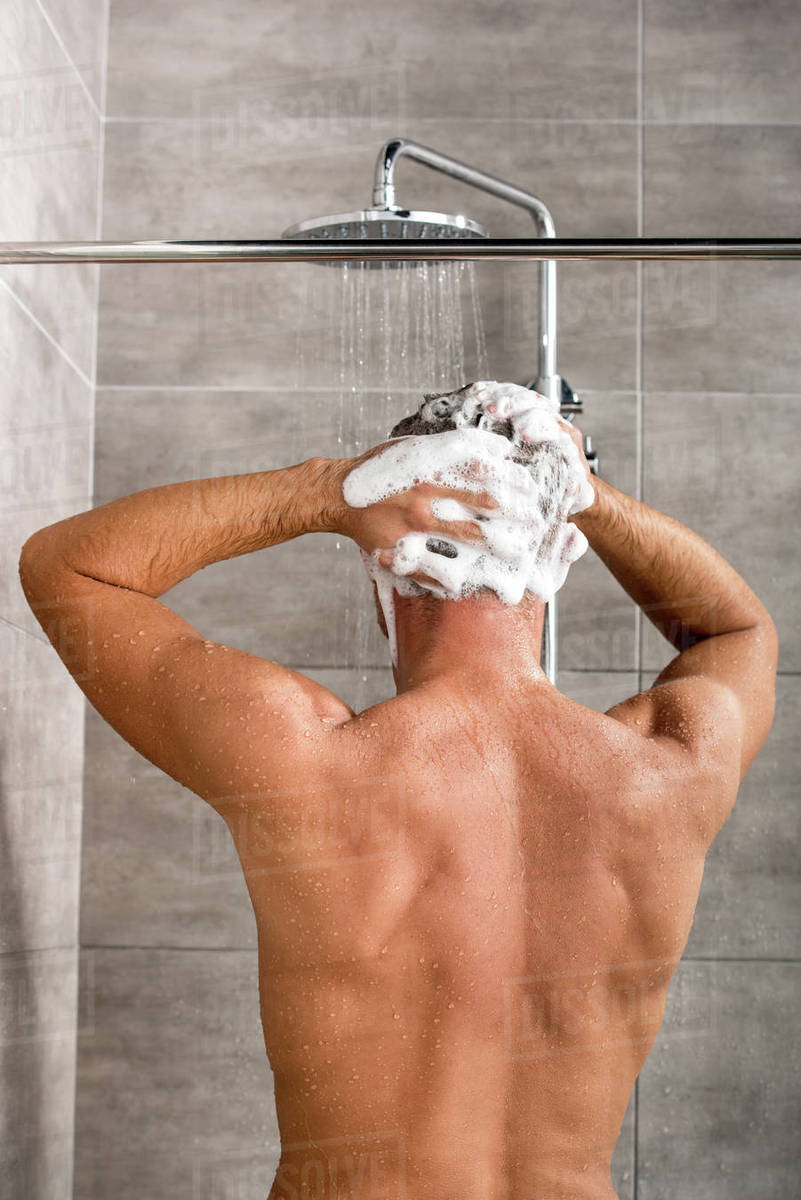 Back view of man washing hair with shampoo and taking shower Royalty-free stock photo