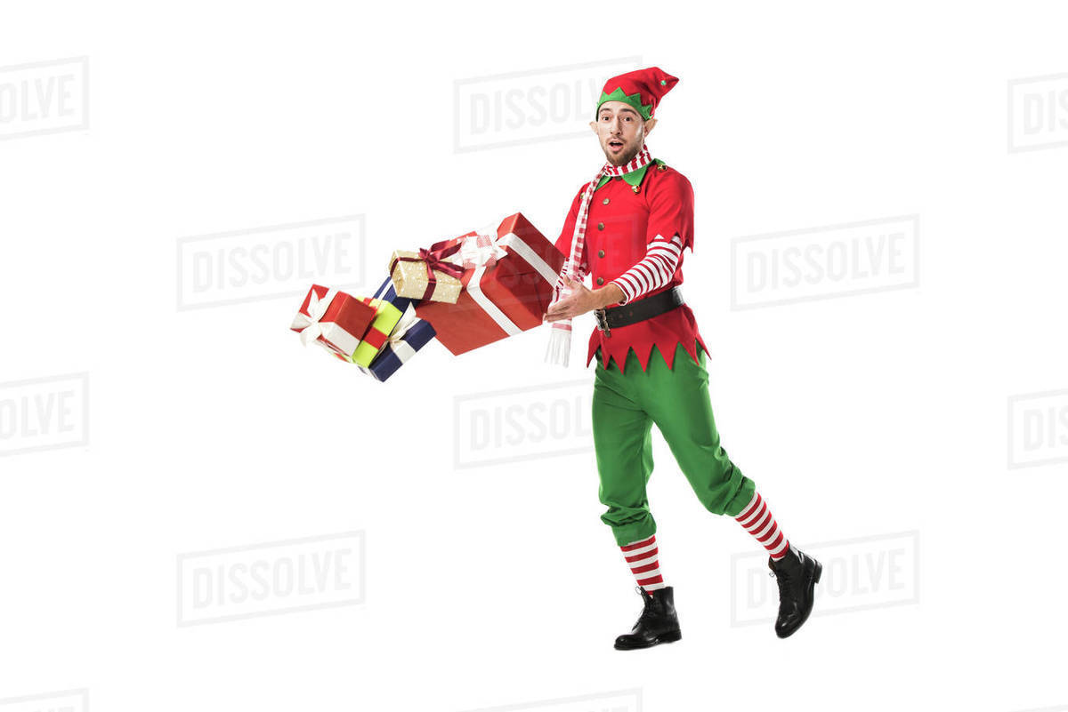Christmas Elf Costume.Surprised Man In Christmas Elf Costume Accidentally Dropping Pile Of Presents Isolated On White Stock Photo