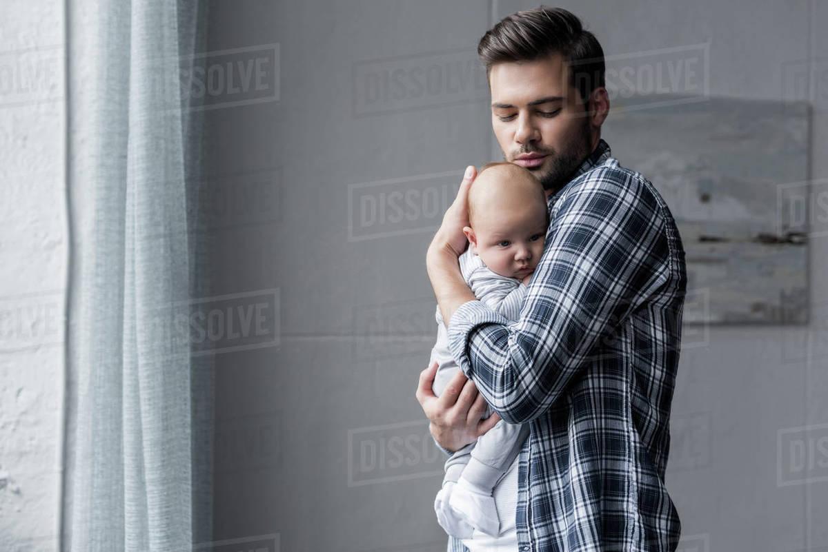 276a543e Handsome father hugging his cute newborn son - Stock Photo - Dissolve