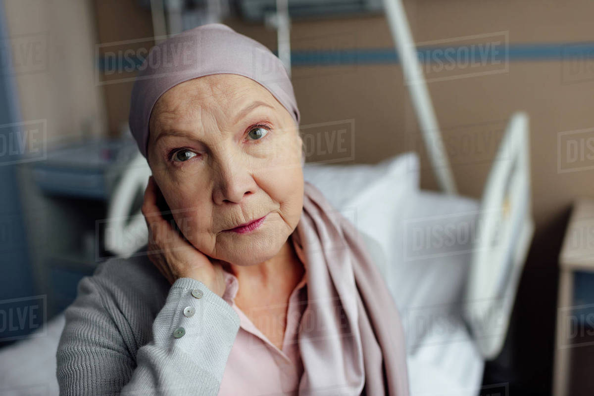 Upset senior woman with cancer sitting on bed in hospital and looking at  camera stock photo