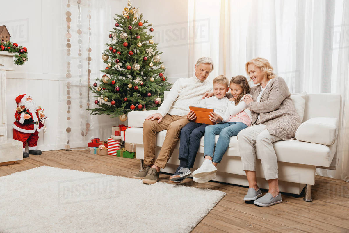 Happy Grandparents And Kids Looking At Tablet On Sofa In D2115 206 013