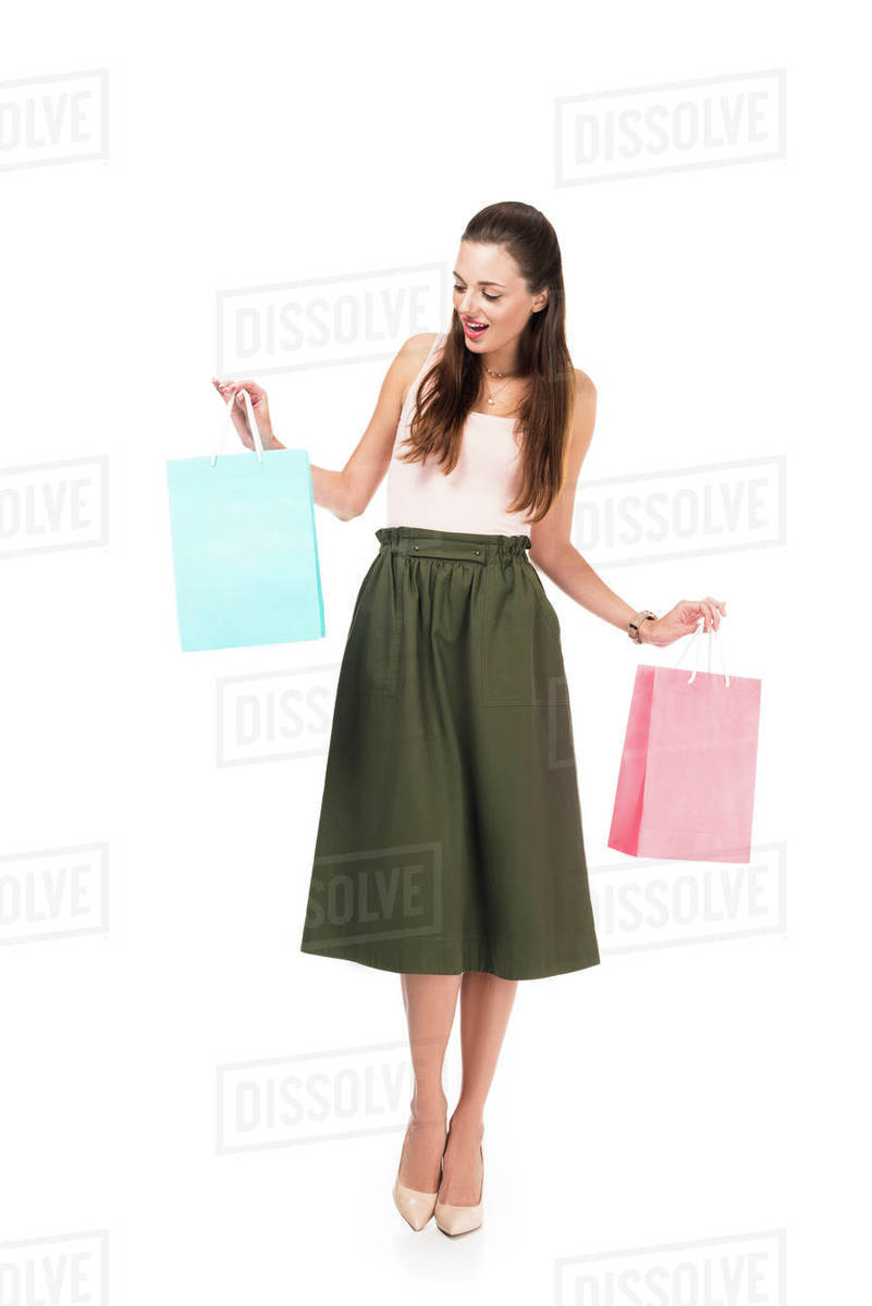 211b065715 Excited young woman holding shopping bags isolated on white - Stock ...