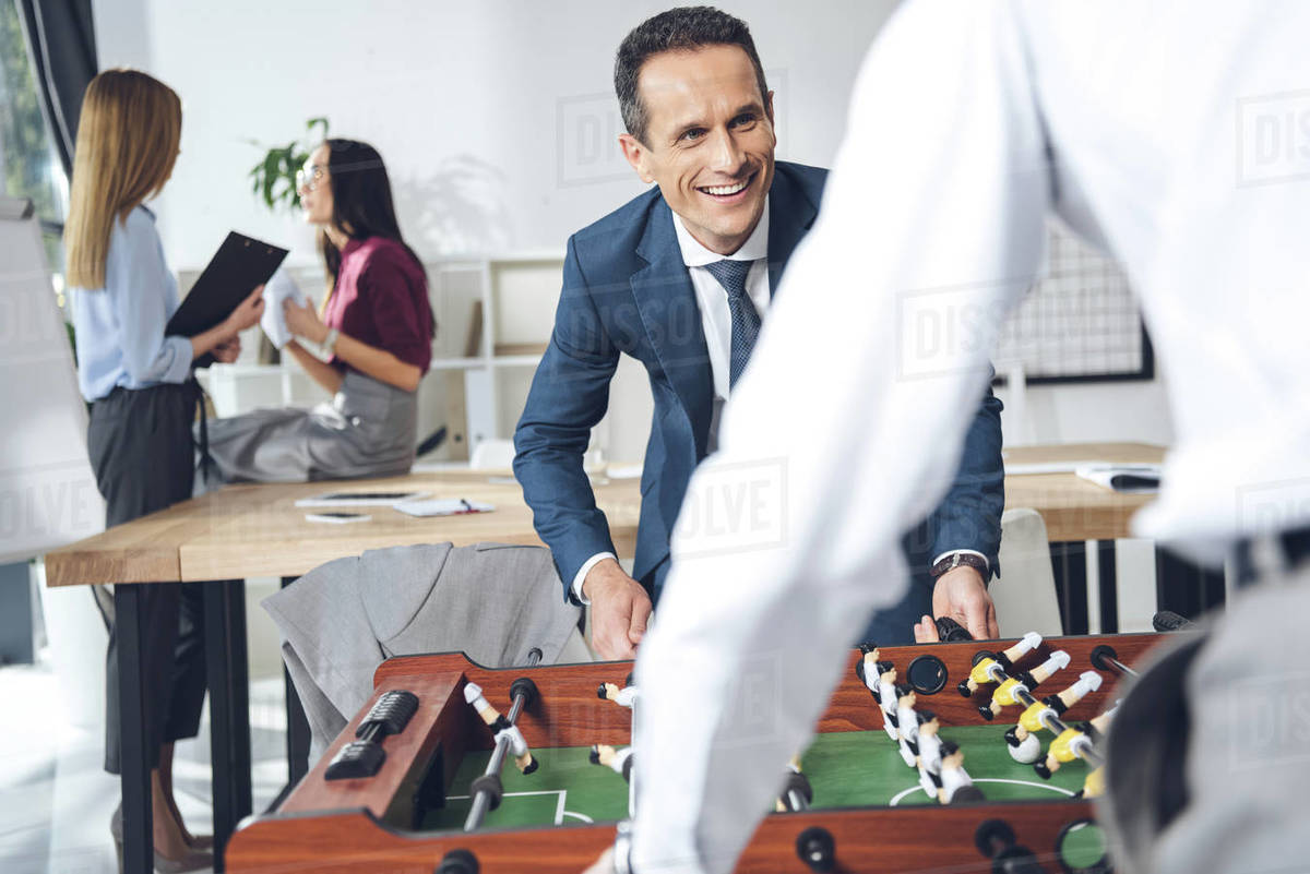 Businessmen Playing Table Football In Modern Office With