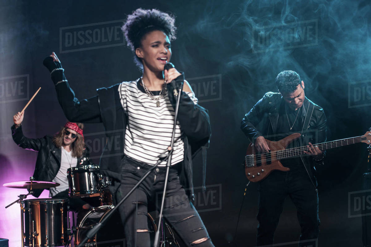 Female Singer With Microphone And Rock And Roll Band Performing Hard Rock Music On Stage Stock Photo Dissolve