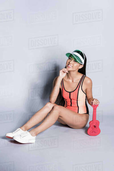 cab26db33d54d Full-length shot of cheerful Asian woman in coral swimsuit and visor  sitting on floor