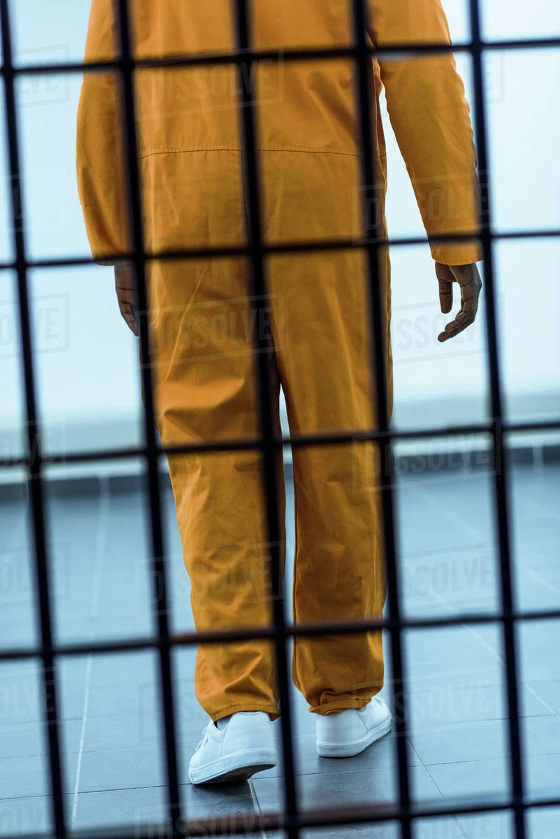 Cropped image of African American prisoner behind prison bars stock photo