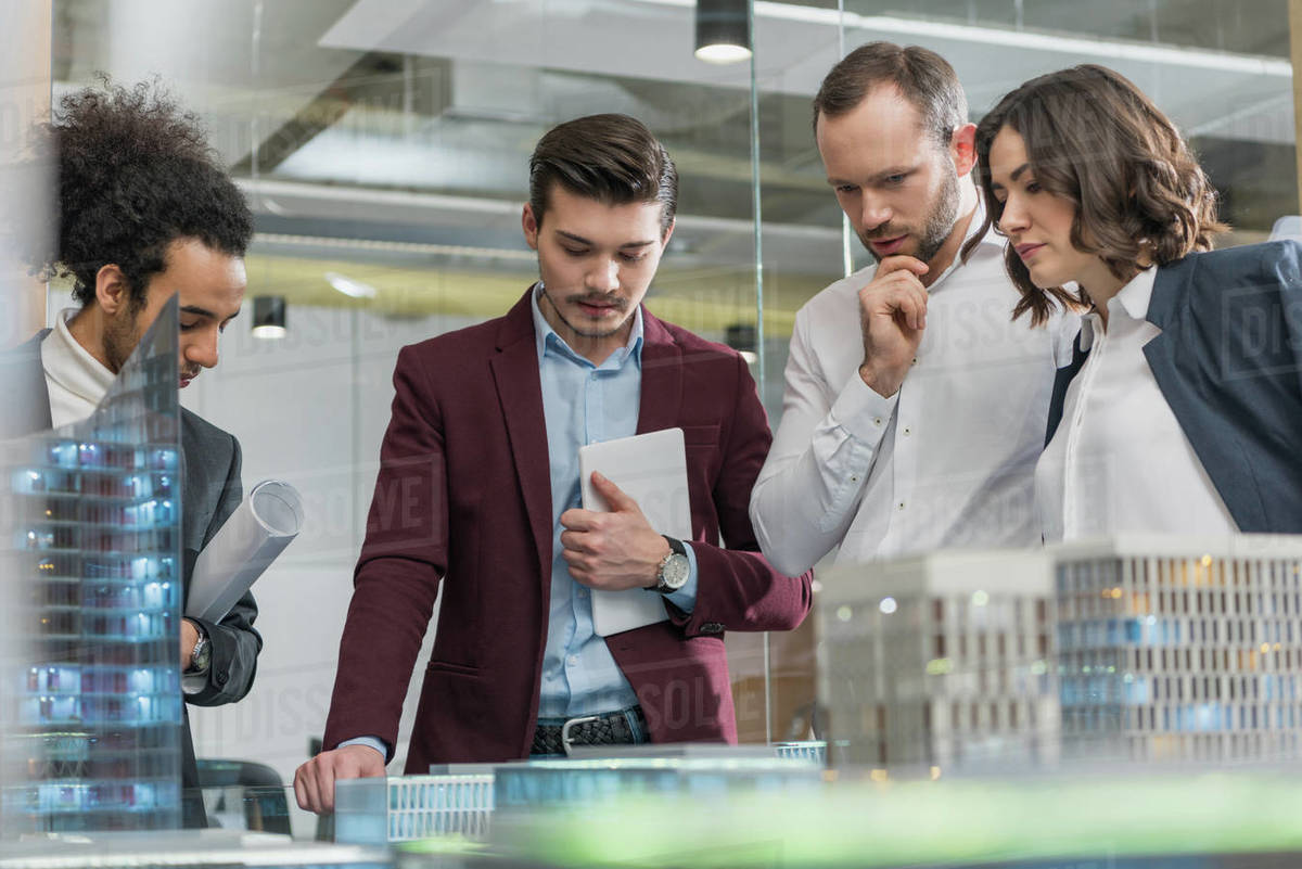 Group of thoughtful architects discussing building models at office Royalty-free stock photo
