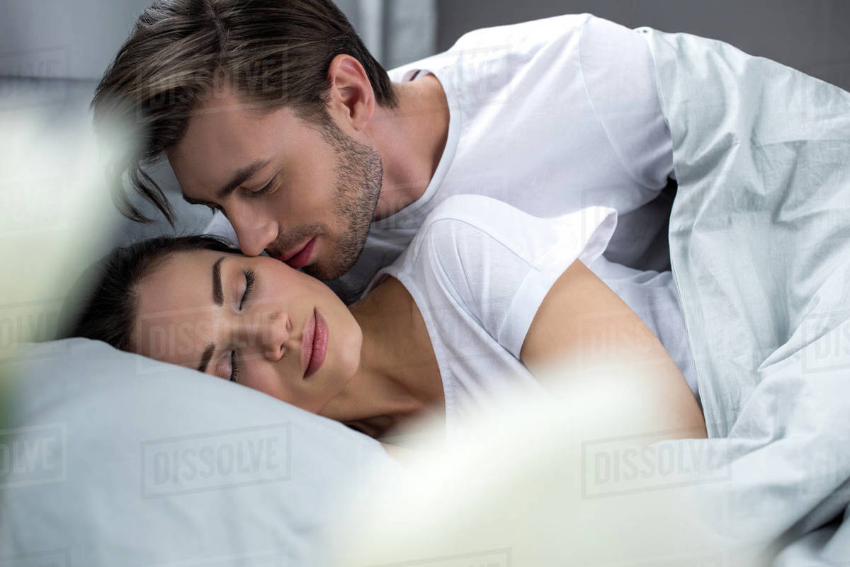 Husband tenderly kissing sleeping wife in bed - Stock Photo - Dissolve