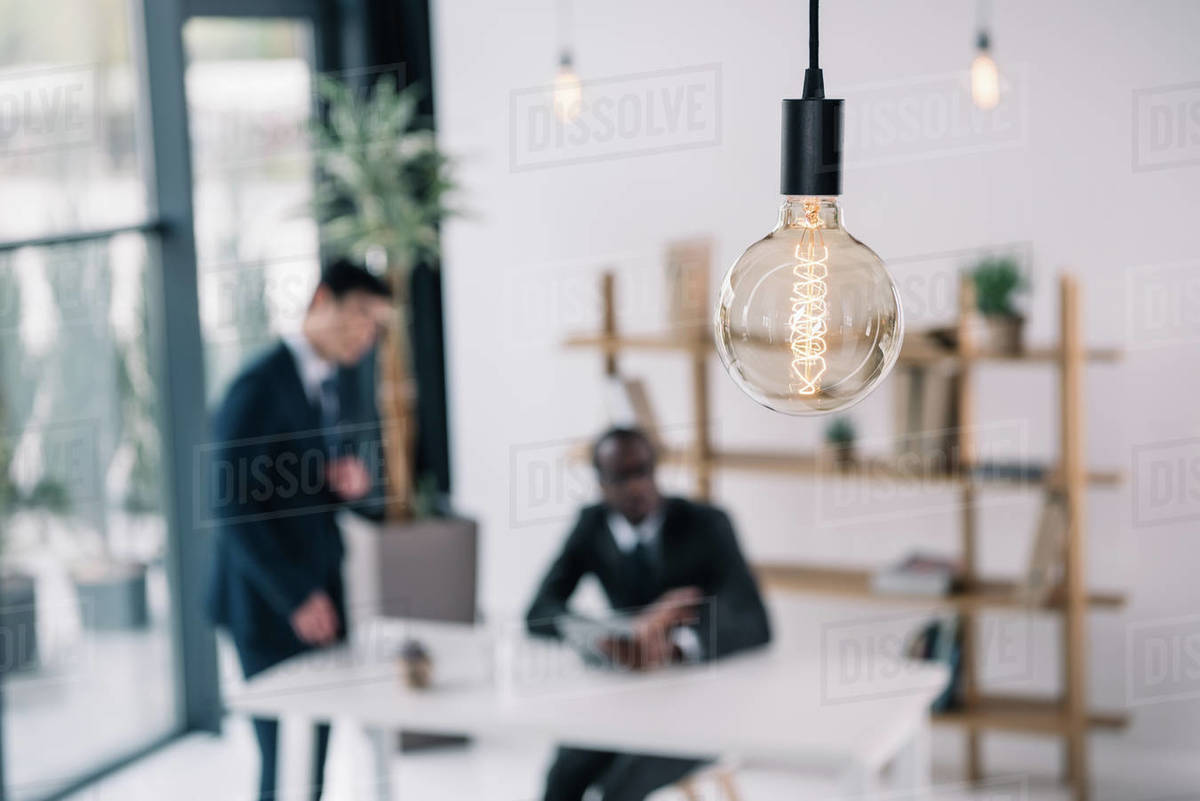 Vintage Lamp With Business Colleagues Sitting In Modern Office