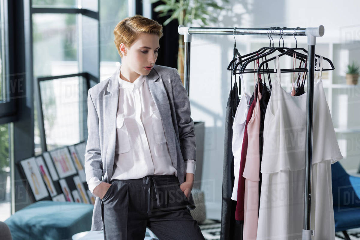 Young Fashion Designer Looking At Clothing On Rack Stock Photo Dissolve