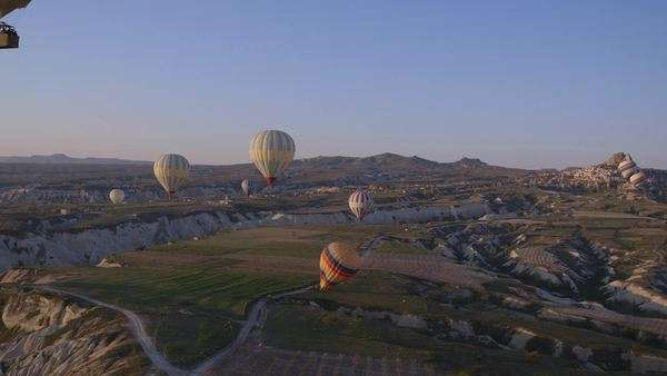 Locked off shot of hot air balloons drifting over a spectacular landscape Royalty-free stock video