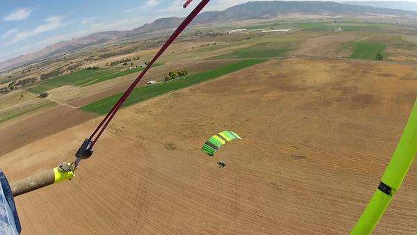 Aircraft parachute ultralight over farm fields. Low level Ultralight flight over rural community and farms. Airborne powered parachute in low level aircraft having fun with extreme recreation. Rolling hills high mountains, rural homes. Royalty-free stock video