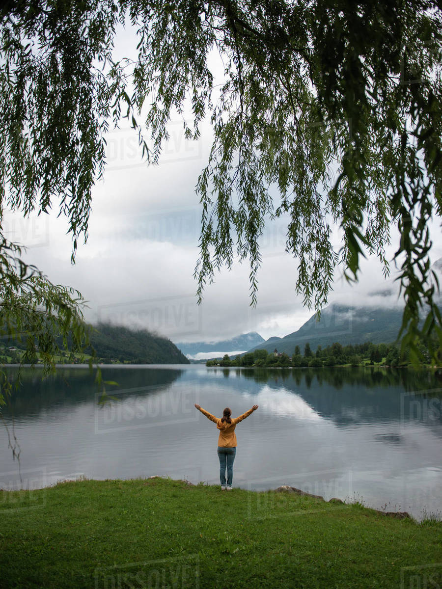 Rear view of woman standing at lake shore with raised arms looking at water and enjoying the view Royalty-free stock photo