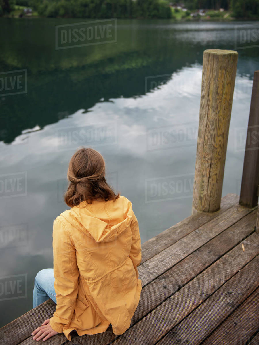 Back view of woman sitting on wooden pier and looking at water  Royalty-free stock photo