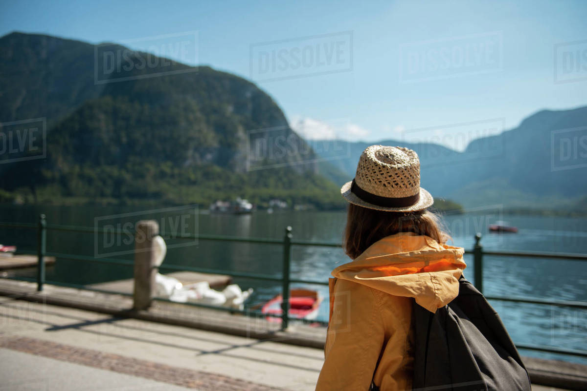 Woman with backpack walking along lake shore and enjoying the scenic view Royalty-free stock photo