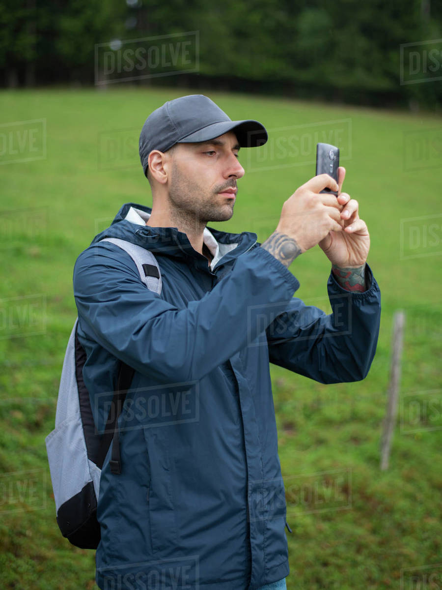 Man standing in forest using camera phone  Royalty-free stock photo