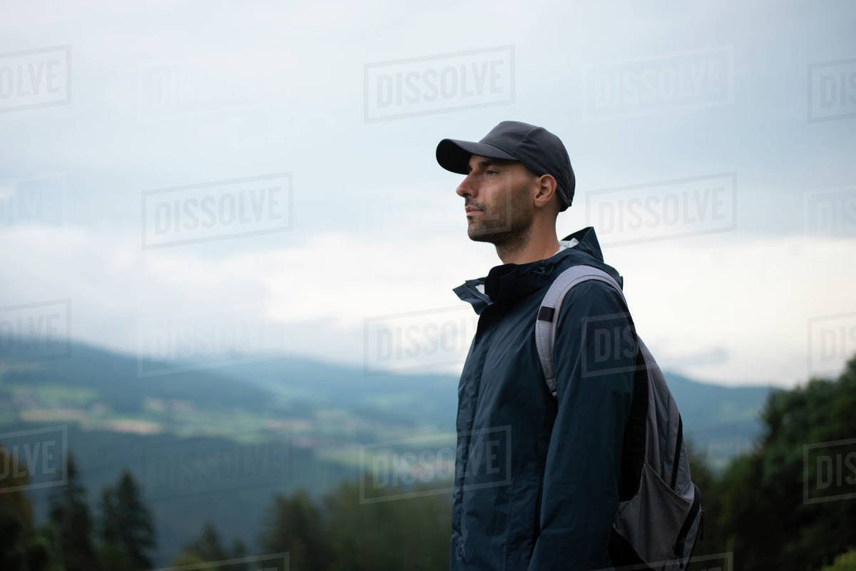 Man with backpack standing in forested mountains looking far distance at dusk Royalty-free stock photo