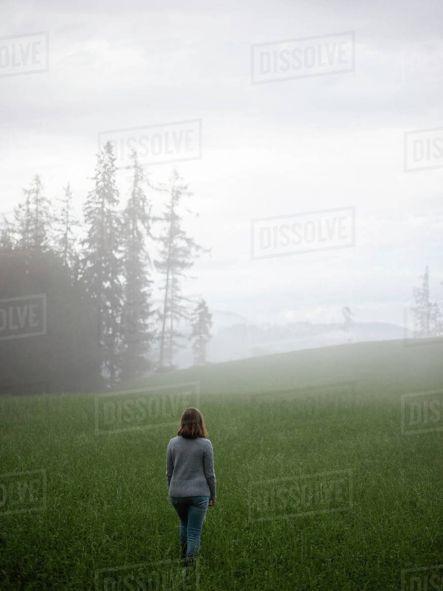 Woman standing in field looking away in fog Royalty-free stock photo