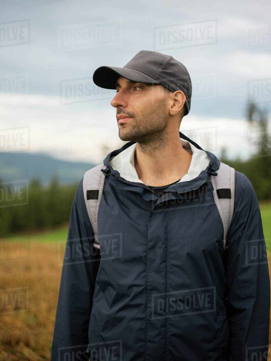 Man with backpack standing and looking away in field against cloudy sky Royalty-free stock photo