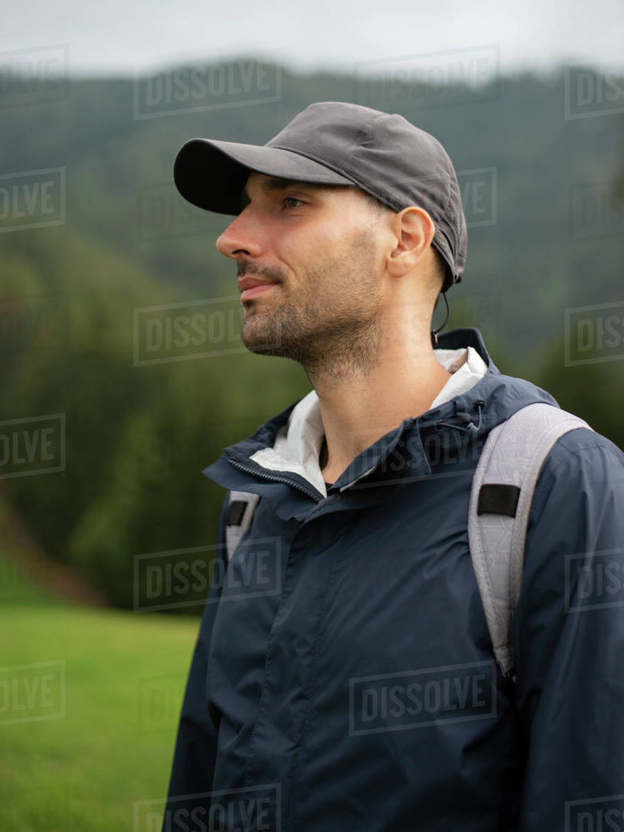 Man with backpack standing in field looking far distance against forest Royalty-free stock photo