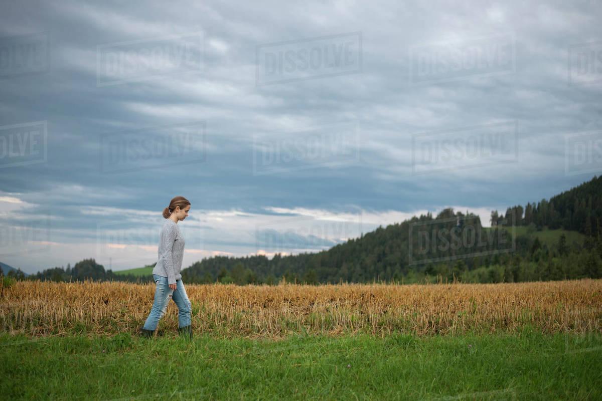 Female farmer walking across field in mountains Royalty-free stock photo