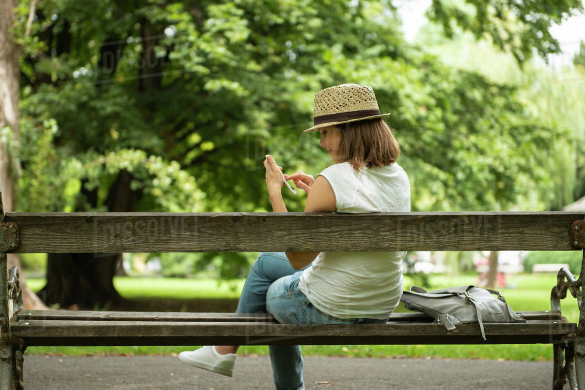 Woman sitting in park using mobile phone  Royalty-free stock photo