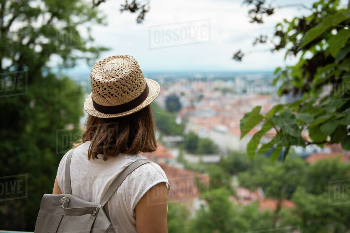Back view of woman looking at cityscape through foliage Royalty-free stock photo