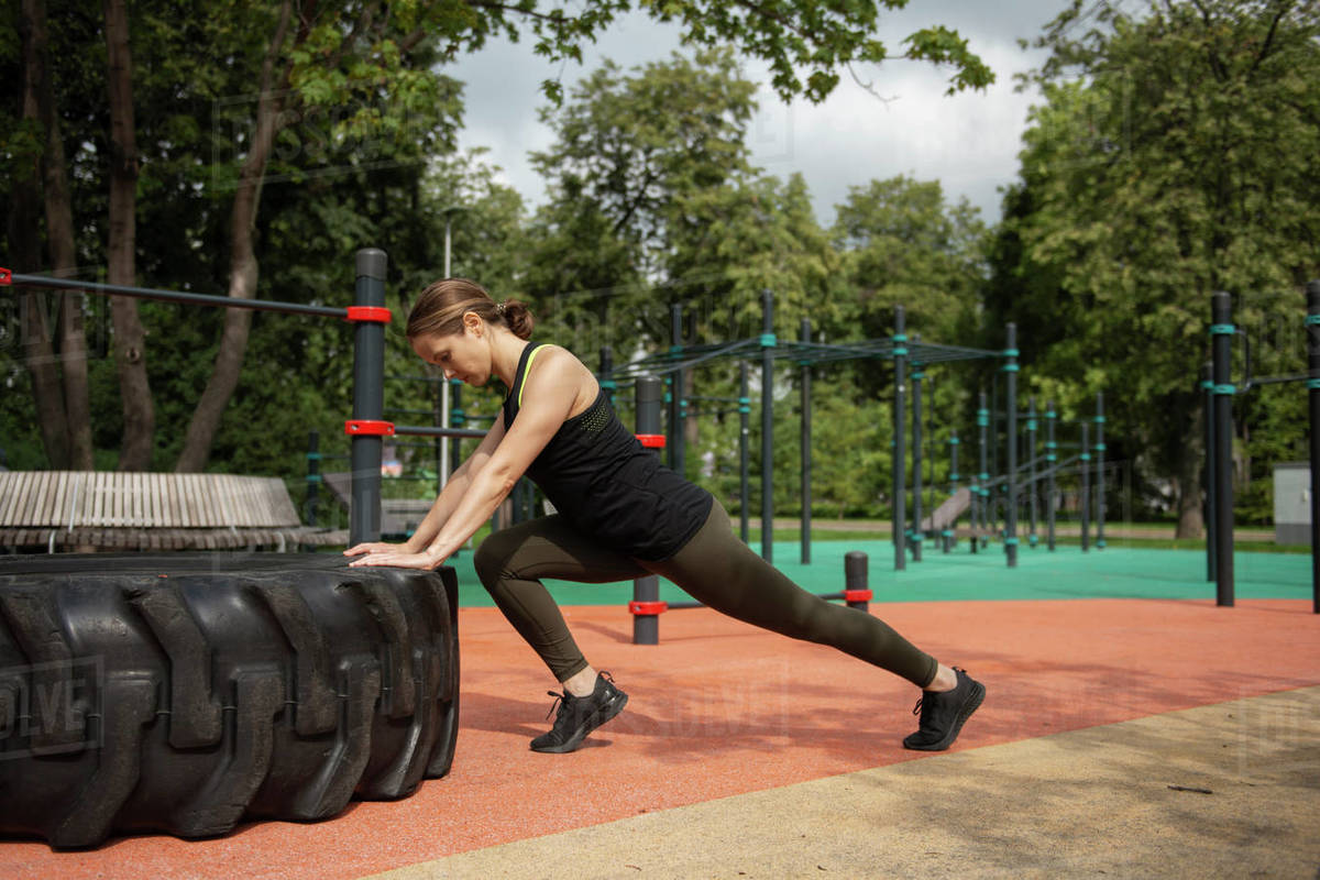 Woman training outdoors pushing heavy tire  Royalty-free stock photo