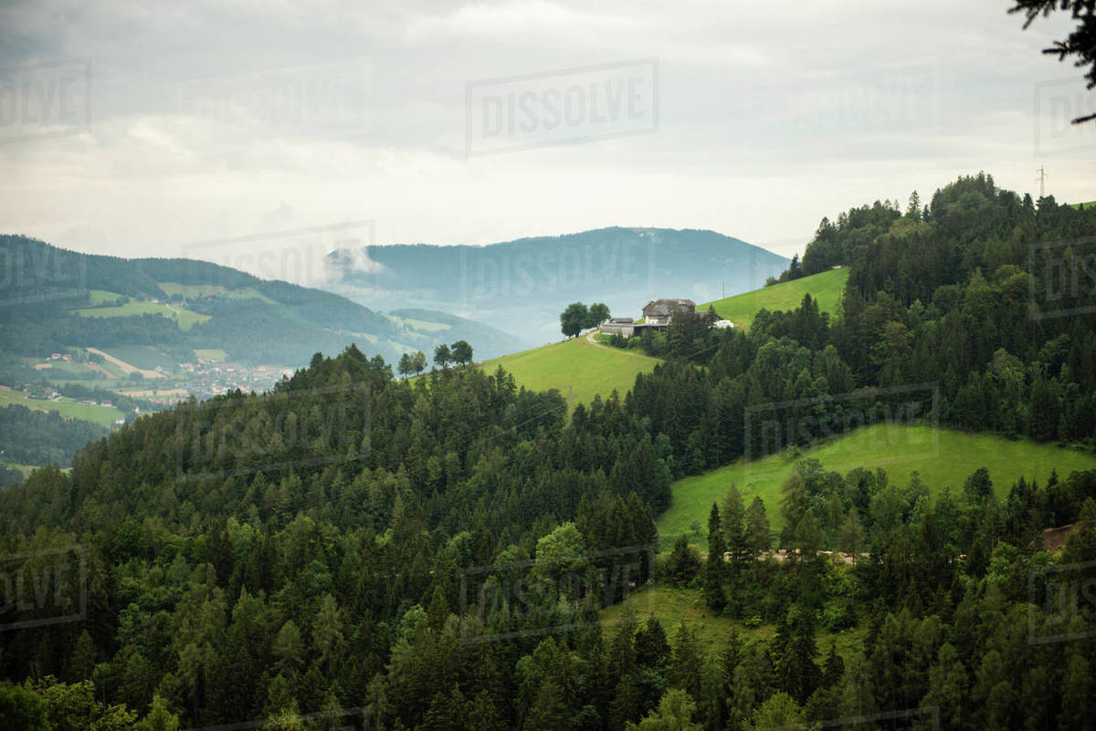 Farmhouse on the hill in mountains during foggy evening Royalty-free stock photo