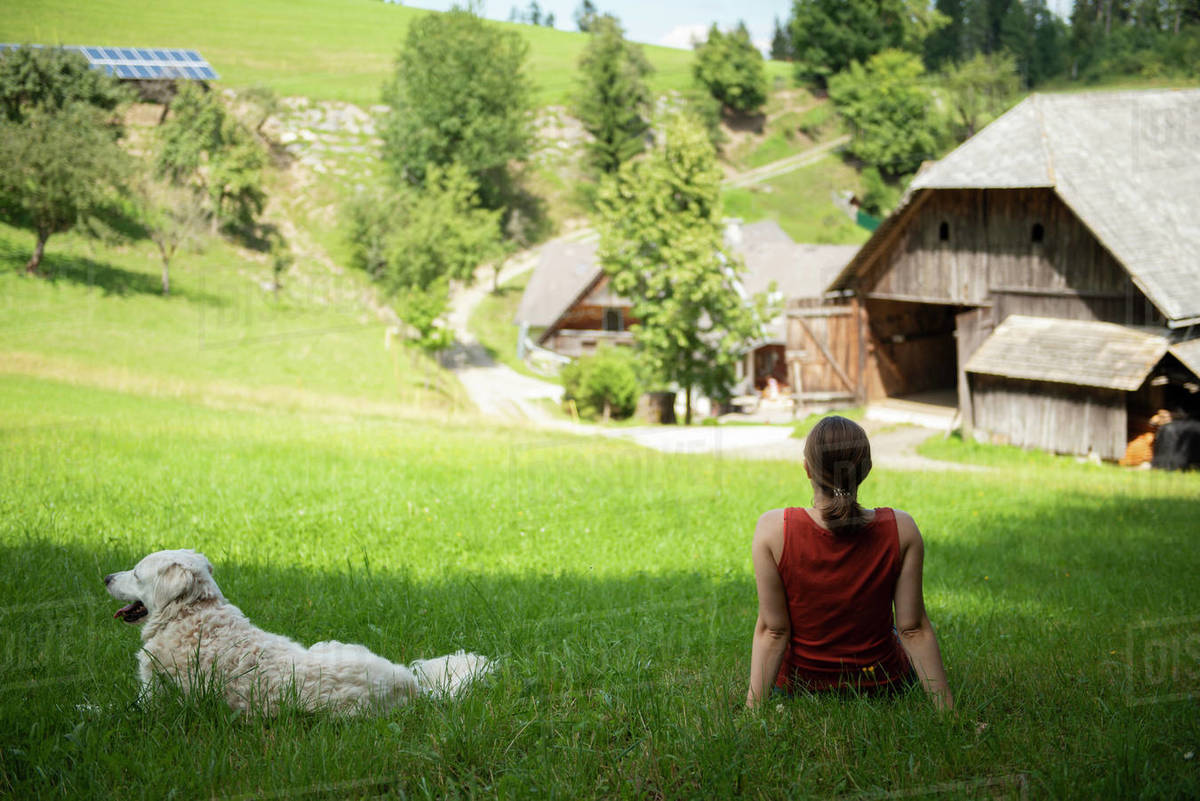 Woman sitting and relaxing on grass with her dog in countryside area Royalty-free stock photo