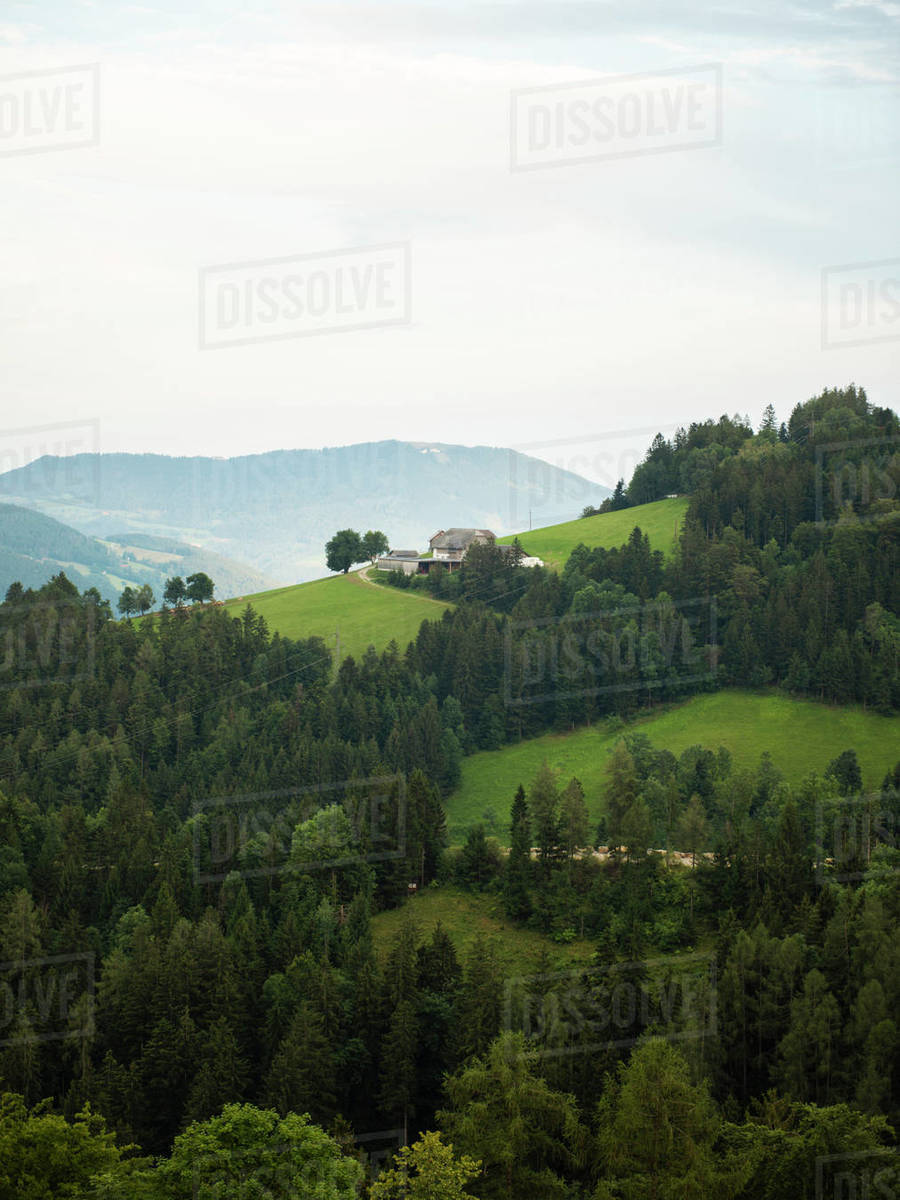 Lonely farmhouse standing on the hill in forested mountains Royalty-free stock photo
