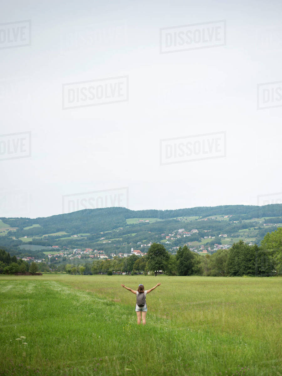 Woman with raised arms standing in field and enjoying summer day Royalty-free stock photo