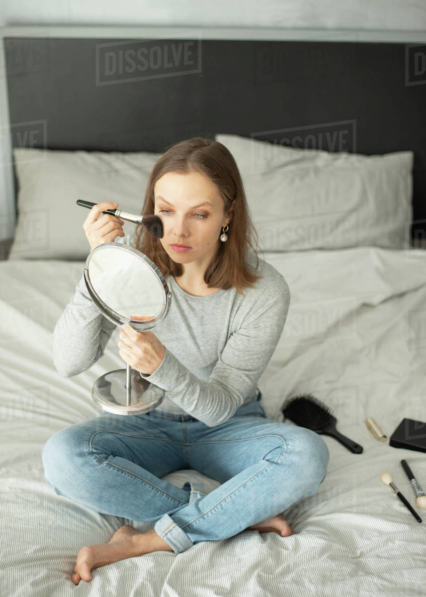 Woman sitting on bed applying makeup on her face Royalty-free stock photo