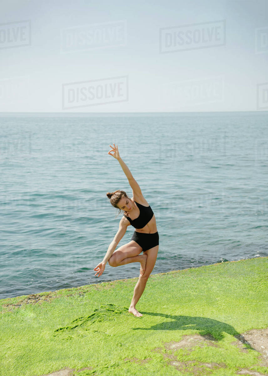 Woman practicing yoga standing on one at seaside  Royalty-free stock photo