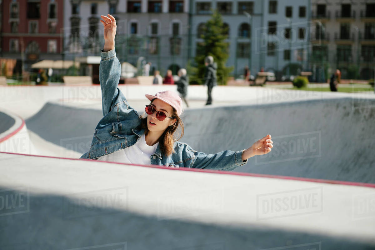 Young woman with raised arms doing skateboarding trick outdoor Royalty-free stock photo