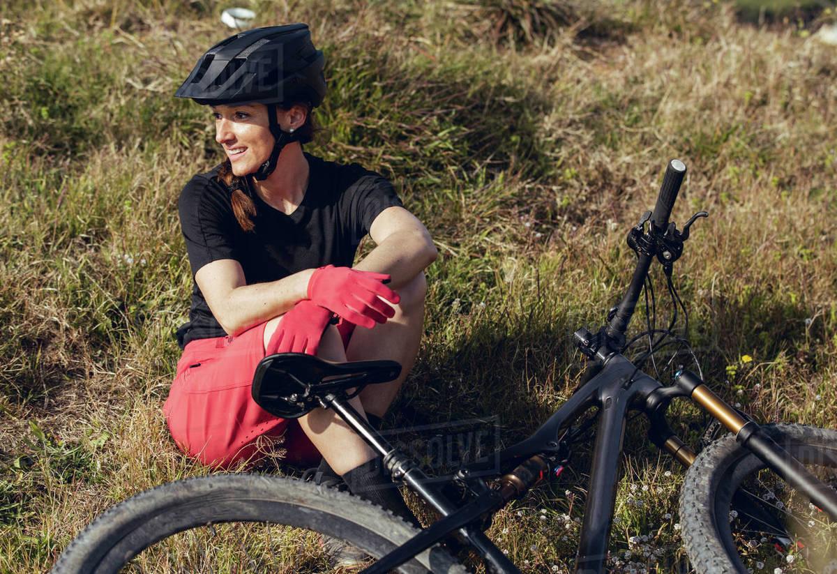 Sportswoman in black helmet and red sportswear sitting resting near training track looking away Royalty-free stock photo