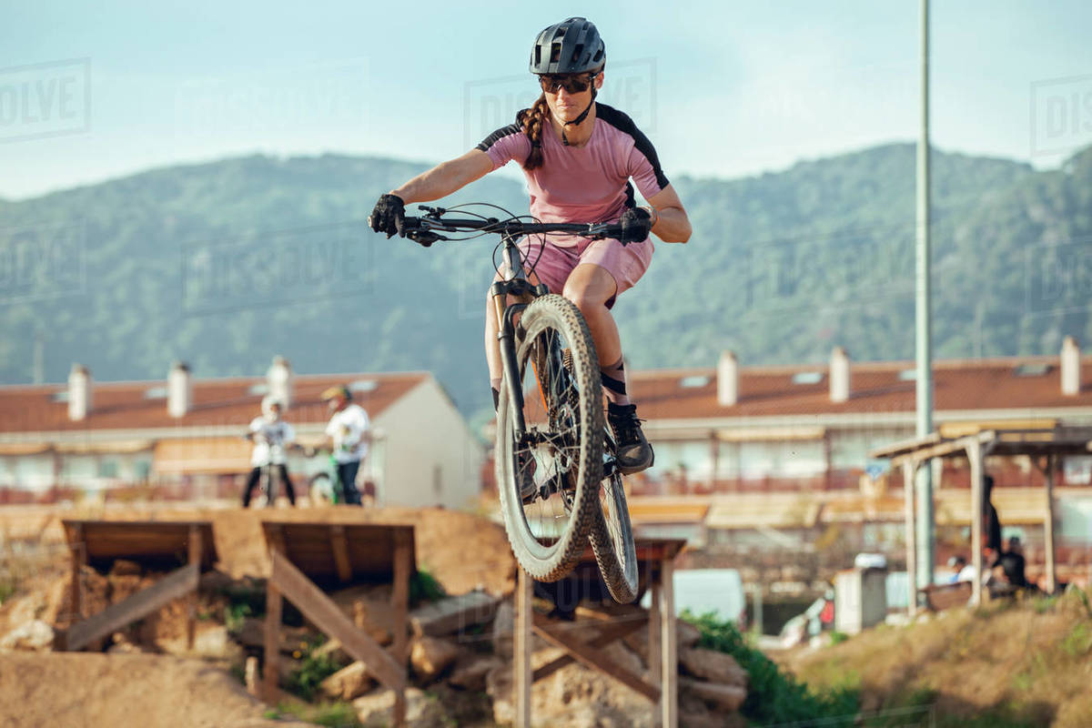 Sportswoman in black helmet and sportswear with glasses riding mountain bike jumping from a bridge in training track Royalty-free stock photo