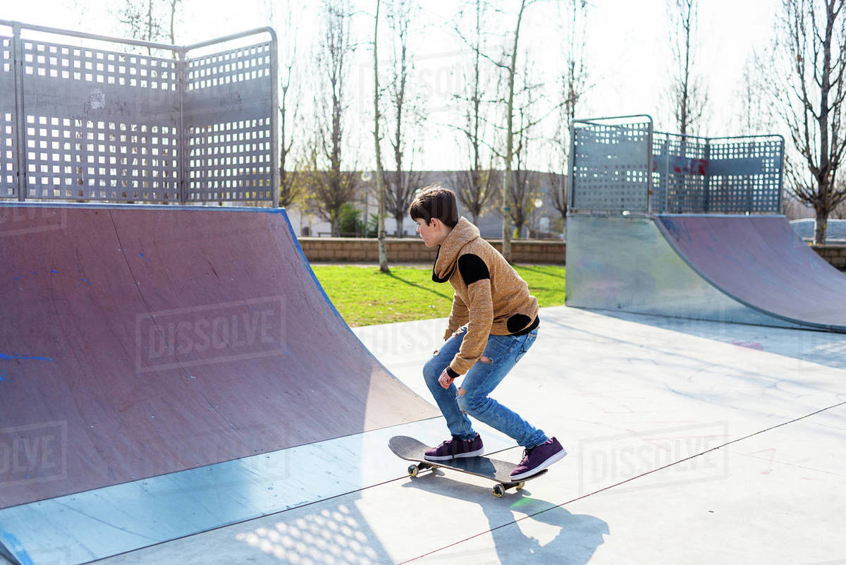 Teenage boy performing trick on skateboard on ramp while practicing tricks on sunny day Royalty-free stock photo