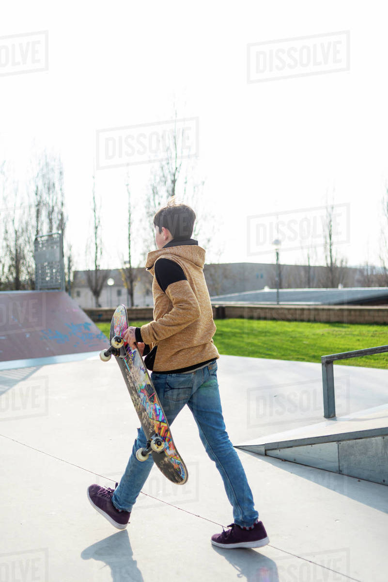Side view of teen boy with skateboard walking in skate park and enjoying weekend Royalty-free stock photo
