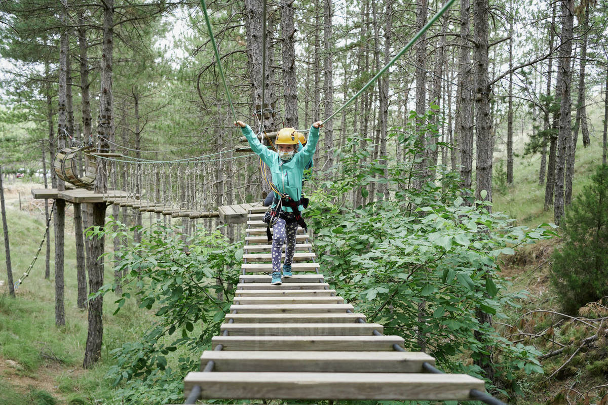Full body girl with helmet and safety harness using self belay and walking on hanging path in adventure park in forest Royalty-free stock photo