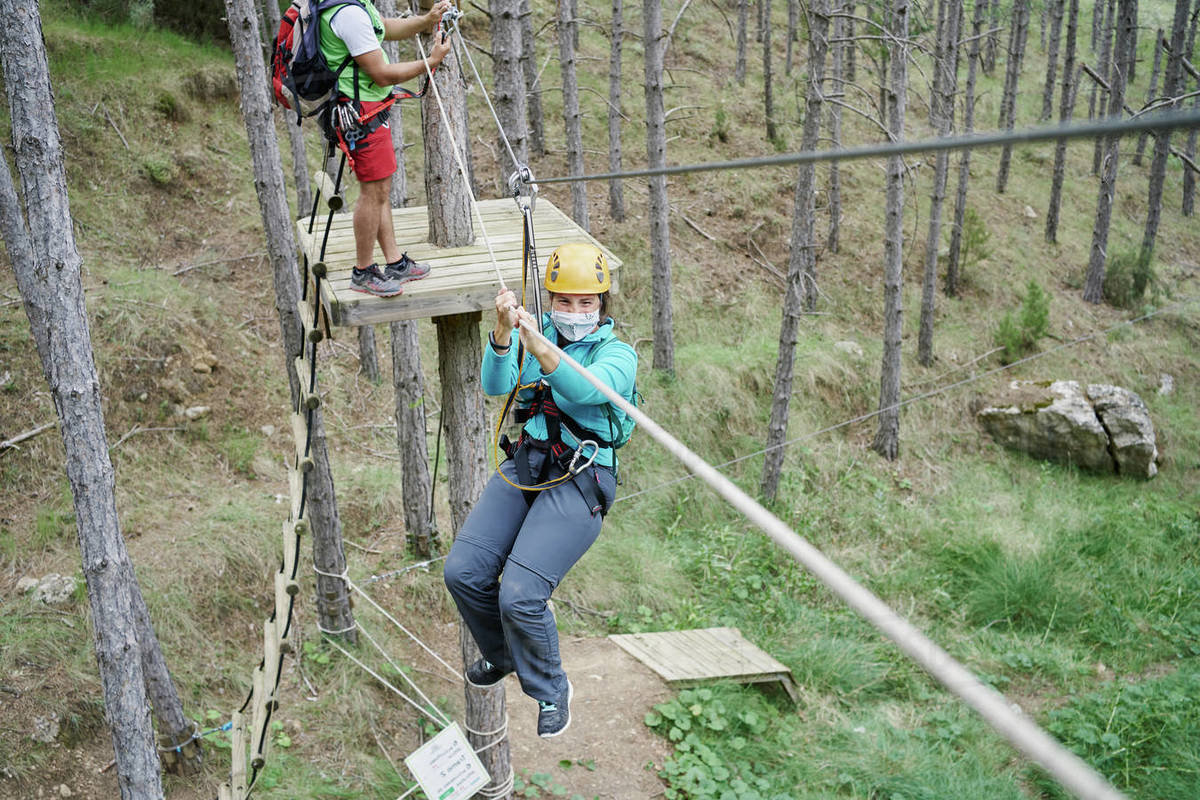 From above female climber in mask and helmet suing harness to ride rope course in adventure park in forest during pandemic Royalty-free stock photo