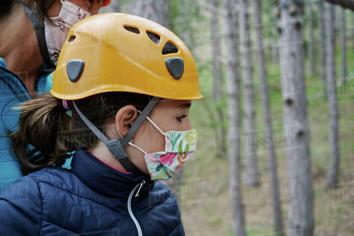 Girl in helmet and face mask grasping rope while climbing obstacle course in adventure park in forest during pandemic Royalty-free stock photo