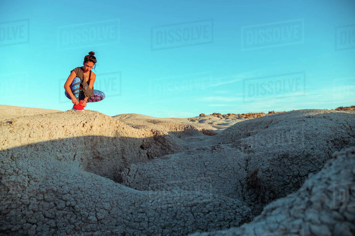 From below active female athlete in sportswear tying shoelaces on sneakers while preparing for workout on rocky slope of rough desert hilly terrain under blue sky Royalty-free stock photo