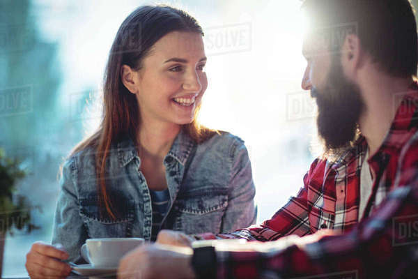 Happy young couple talking at cafe Royalty-free stock photo