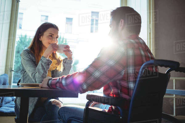 Happy woman looking at disabled boyfriend at cafe Royalty-free stock photo